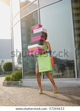 hispanic woman balancing stack of shoe boxes out of shopping center. Vertical shape, full length, copy space - stock photo