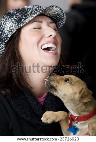 Hispanic woman being licked on the neck by small dog - stock photo
