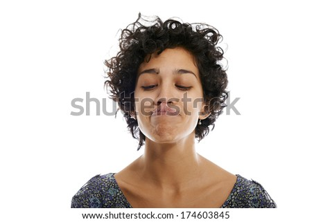 hispanic woman doing facial expression and touching nose with tongue on white background