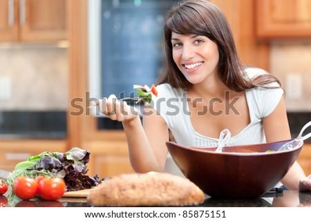 Hispanic woman eating salad - stock photo