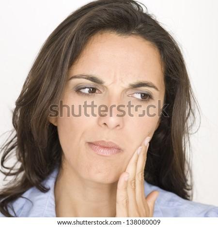 Hispanic woman having toothache - stock photo