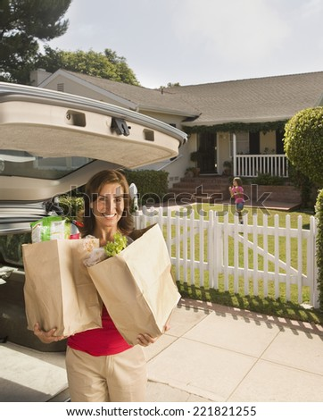 Hispanic woman holding groceries in front of house - stock photo