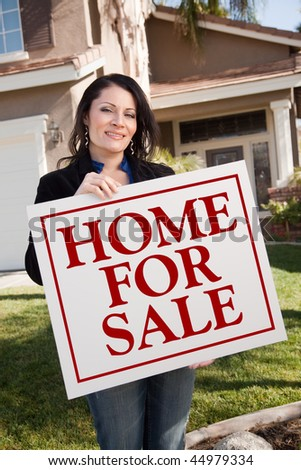 Hispanic Woman Holding Home For Sale Real Estate Sign In Front of House. - stock photo