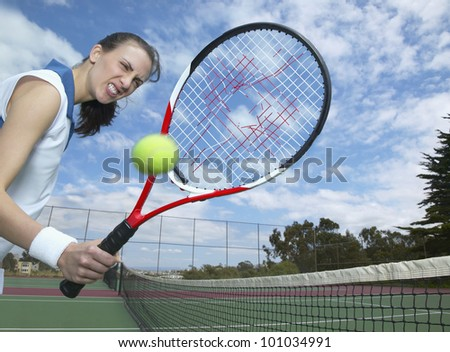 Hispanic woman holding tennis racket with hole in it - stock photo