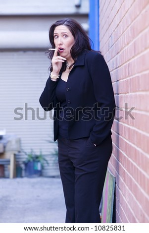 Hispanic woman in an alley caught smoking a cigarette - stock photo