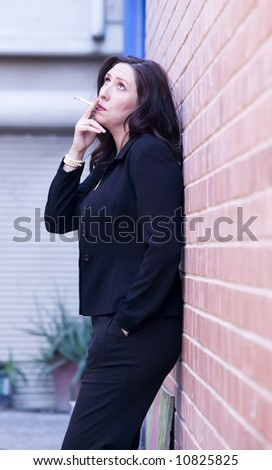 Hispanic woman in an alley smoking a cigarette - stock photo