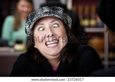 Hispanic woman in hat crossing her eyes - stock photo