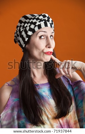 Hispanic woman in tie-dye shirt thinking about something - stock photo