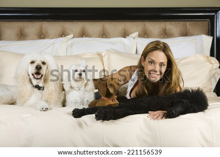 Hispanic woman laying on bed with dogs - stock photo
