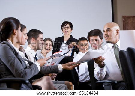 Hispanic woman leading diverse group of young business people in training seminar - stock photo