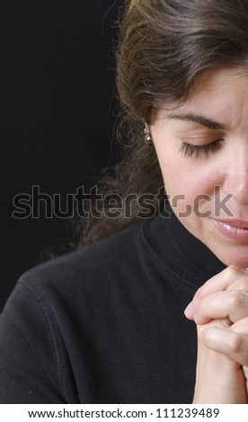 Hispanic woman praying and praising the Lord - stock photo