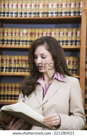 Hispanic woman reading library reference book - stock photo