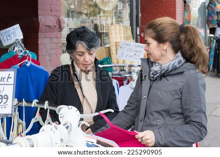 Hispanic woman shopping in Chinese store or shop in Chinatown which is an ethnic enclave in Downtown Toronto with a high concentration of ethnic Chinese residents and businesses. - stock photo