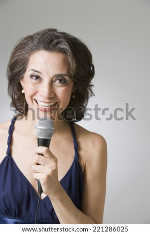 Hispanic woman singing into microphone - stock photo