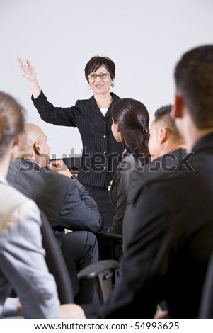 Hispanic woman standing in front, speaking to group of business people - stock photo