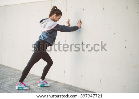 Hispanic woman stretching before her running workout - stock photo