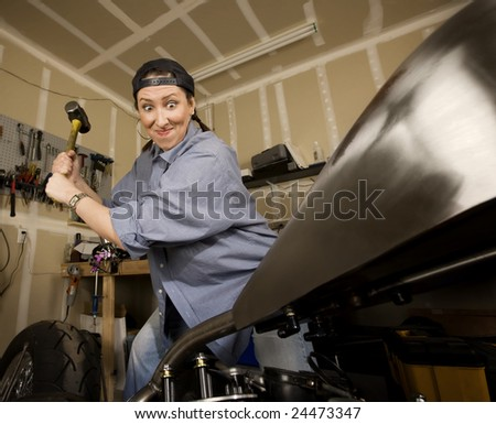 Hispanic woman swinging a sledgehammer at a motorcycle - stock photo