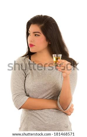 hispanic woman taking a tequila shot - stock photo
