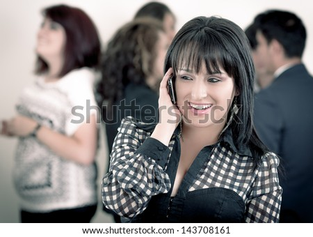 Hispanic woman using a cellphone with peers - stock photo
