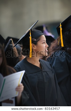 Hispanic woman wearing graduation hat and gown - stock photo