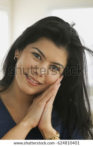 Hispanic woman with hands clasped