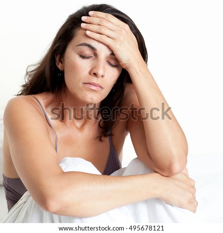 Hispanic woman with headache in bed