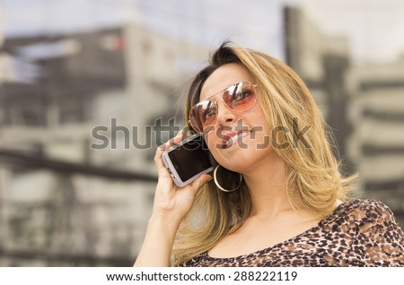 Hispanic woman with sunglasses outdoors talking on phone - stock photo