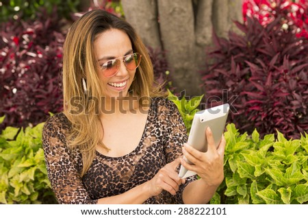 Hispanic woman with tablet outdoors wearing sunglasses and reading - stock photo