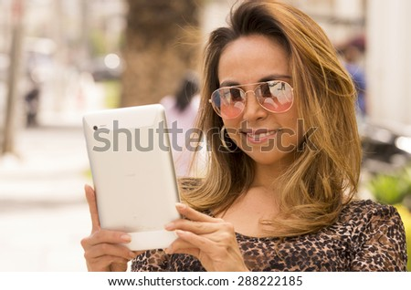 Hispanic woman with tablet outdoors wearing sunglasses and reading and smiling - stock photo
