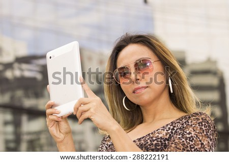 Hispanic woman with tablet outdoors wearing sunglasses posing - stock photo