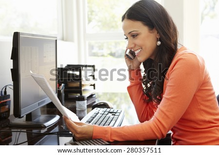 Hispanic woman working in home office - stock photo