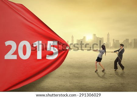 Hispanic women try to pull number 2015 at sunset, symbolizing a change for bright future - stock photo