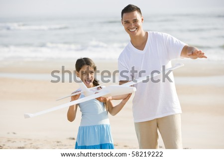 Hispanic 9 year old girl and father playing with toy airplane on beach - stock photo