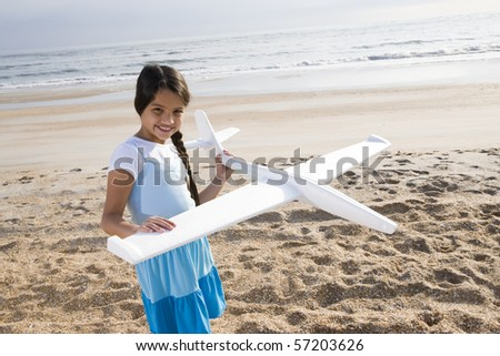 Hispanic 9 year old girl playing with toy plane on beach - stock photo