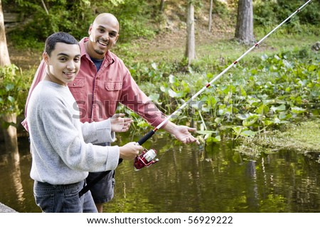 Hispanic 14 year old teen boy and father fishing in pond - stock photo