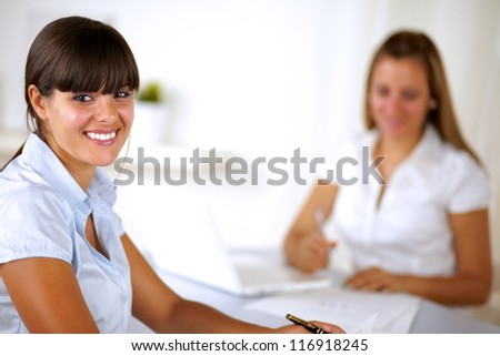 Hispanic young businesswoman looking at you at office while working on team - stock photo