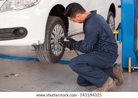 Hispanic young mechanic using an air gun to tighten the bolts of a tire from a suspended car - stock photo