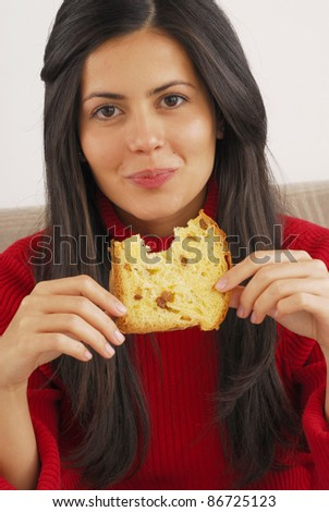 Hispanic young woman eating panettone,Young woman eating bread. - stock photo