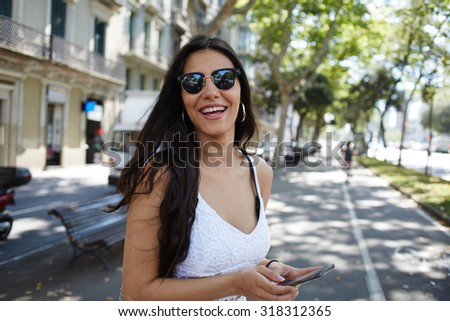 Hispanic young woman enjoying summer walk in the city feeling joy and happy while smiling to the camera, attractive female laughing just received good message on mobile phone while strolling outdoors - stock photo