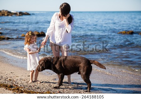 Hispanic young woman relaxing and walking at the beach with her daughter and her dog