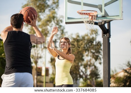 Hispanic young woman trying to block his boyfriend's shot during a basketball game outdoors - stock photo