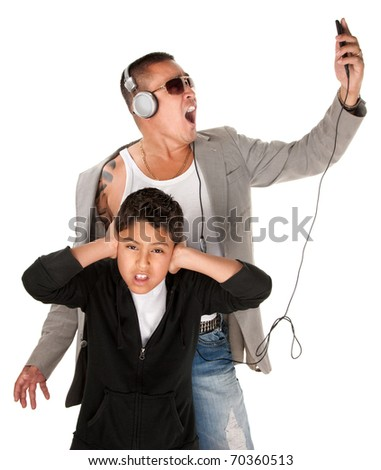 Hispanic youngster covers ears while father sings to music from an mp3 player - stock photo