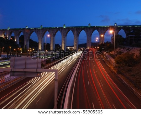 historic aqueduct in the city of Lisbon built in 18th century (car blur motion) - stock photo