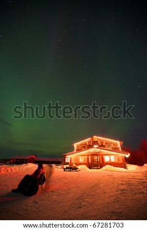 Historic Bettles Lodge in a snow-covered setting, brightly light under the Aurora Borealis. - stock photo