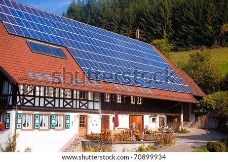 Historic Black Forest (Germany) farm house with modern solar panels on large roof. - stock photo
