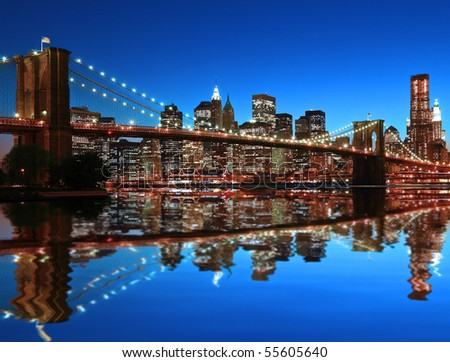 Historic Brooklyn Bridge and lower Manhattan reflected in East River - stock photo