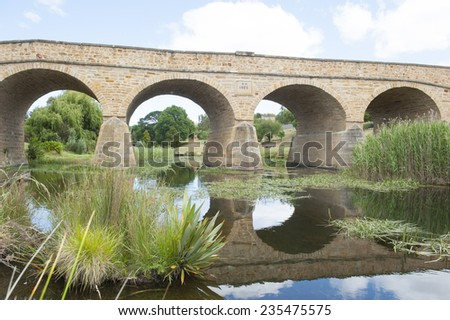 Historic building in heritage listed Richmond, Tasmania, oldest convict built stone bridge in Australia, with mirror image in water of river beneath arches, tourist attraction close to Hobart. - stock photo