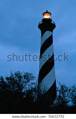 historic cape hatteras lighthouse, illuminated before dawn against cloudy winter sky in 2006, long exposure