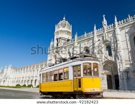 historic classic yellow tram of Lisbon built partially of wood in front of famous Jeronimos monastery, Portugal - stock photo