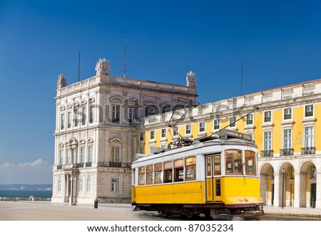 historic classic yellow tram of Lisbon built partially of wood in front of Lisbon central square Praca de Comercio, Portugal - stock photo